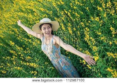 Freedom girl enjoying with flowers on field