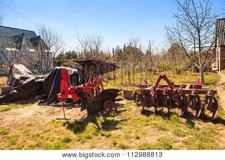 Large Tractor-drawn Plough Seeder In Country Garden In Spring