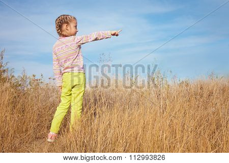Little Girl In Bright Clothes Shows A Finger To The Sky
