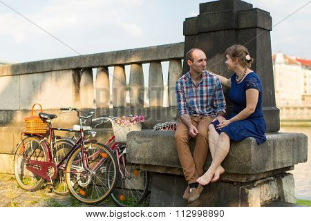 Young couple with bicycles sitting on the parapet.