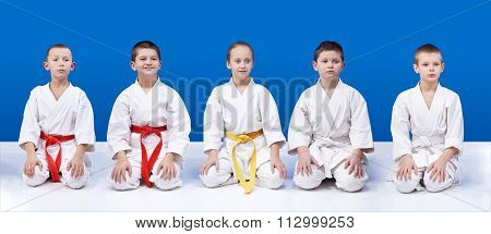 Five athletes in karate sit in positions of karate