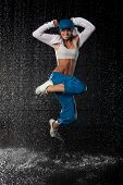 stock photo of dancing rain  - The beautiful girl dancing in water under rain on a black background - JPG