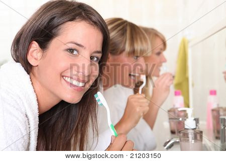 Three young women brushing their teeth
