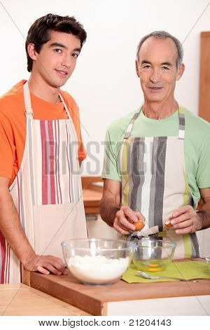 a young man and an old man making a cake