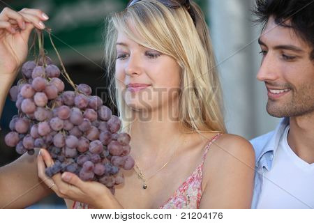 couple looking at huge bunch grapes