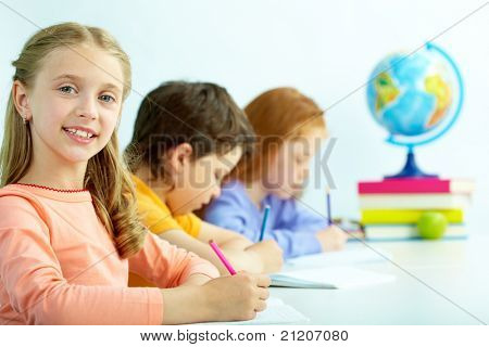 Portrait of smart schoolgirl looking at camera at drawing lesson
