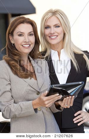 Two smart women in business or businesswomen outside using a tablet computer