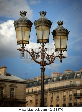 Lamps Against A Partly Cloudy Sky Outside Of Notre Dame Cathedral In Paris, France.