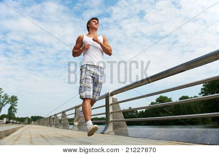 Young positive man jogging in park outdoors