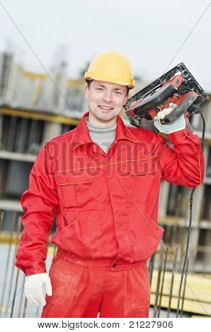 Portarait of positive Builder worker with metal circular saw cuting machine at construction site