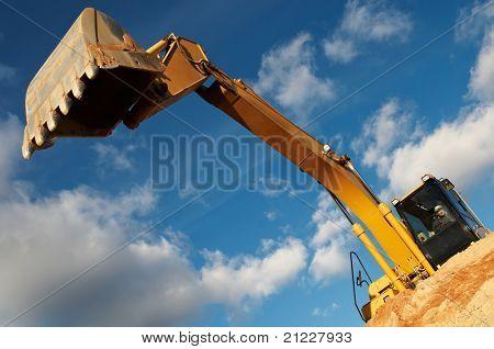 excavator loader machine with risen boom construction site
