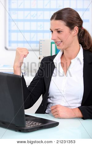 Young businesswoman delighted with what she can see on her computer screen