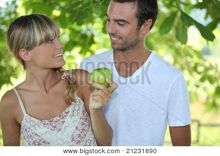 a blonde woman and a man are looking at each other, the woman is taking an apple, the background is forestry