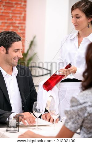 wine waitress showing a wine bottle to a customer