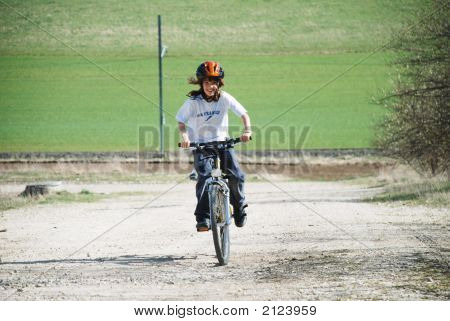 Child Riding Towards Camera On Bicycle In Countryside