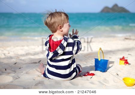 Cute toddler boy playing with beach toys on a tropical beach