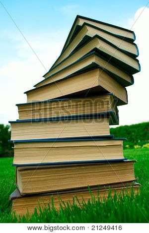 A Stack Of Books Lying On Green Grass