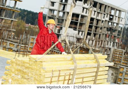 slinger builder in uniform and helmet operating with straps at construction area