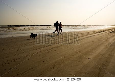 Man And Woman Jogging On The Beach With Their Dog