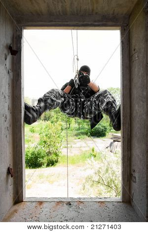 Soldier In Black Mask Entering Through The Window