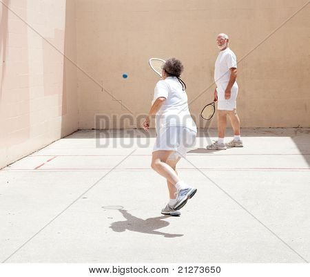 Fit senior couple playing racquetball together on a public court.
