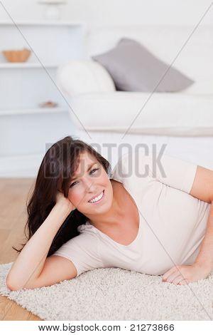 Charmante Brünette Frau, die beim liegen auf einem Teppich