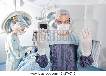 Male surgeon asking for gloves in middle of operation