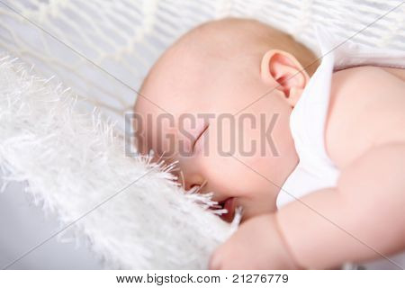 Portrait of a baby girl sleeping on a light background