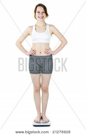 Teenage Girl Standing On Bathroom Scale Smiling