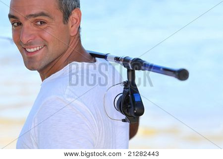 a 40 years old man walking on the beach with a fishing rod on his shoulder