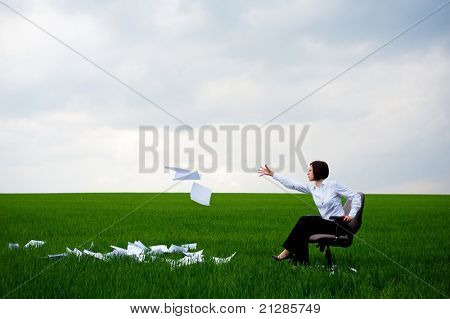 manager sitting on armchair and fling documents on green meadow