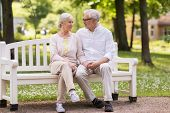 old age, relationship and people concept - happy senior couple sitting on bench at summer park poster