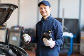 Portrait of an auto mechanic putting oil in a car engine poster