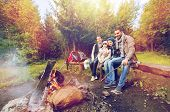 camping, travel, tourism and hike concept - happy family sitting on bench and talking at camp near c poster
