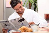 pic of current affairs  - Man at kitchen table having breakfast - JPG