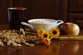 Oat Ears Stems And Oat Flakes In A White Pot, Marigold Flowers And Cup Of Milk And Apple On Dark Bro poster