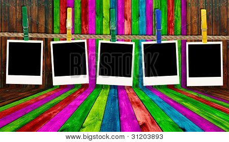 Blank Photos Hanging On Rope On Multicolored Wood Background