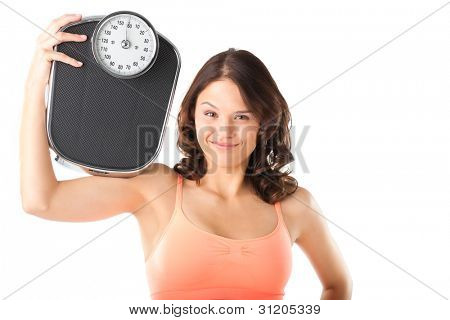 Diet and weight - young woman with a scale, she is happy about the success