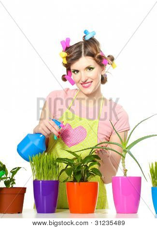 beautiful happy young housewife sprays plants in flowerpots isolated on white