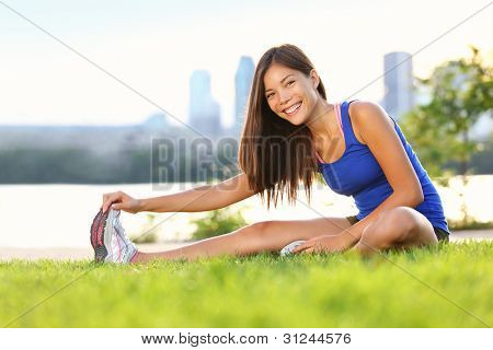 Exercise woman stretching hamstring leg muscles during outdoor running workout. Smiling happy mixed race Asian Chinese / Caucasian sport fitness model in city park.
