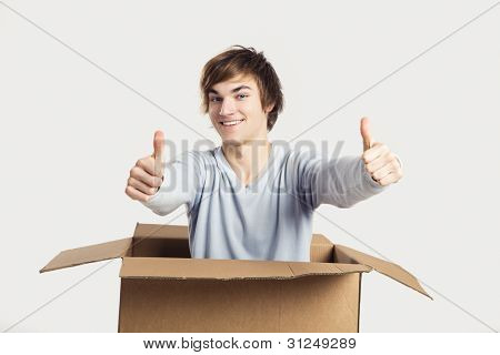 Portrait of a handsome young man a cardbox with thumbs up