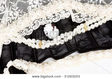 Black lace with form flower, pearls and antique cameo on white background