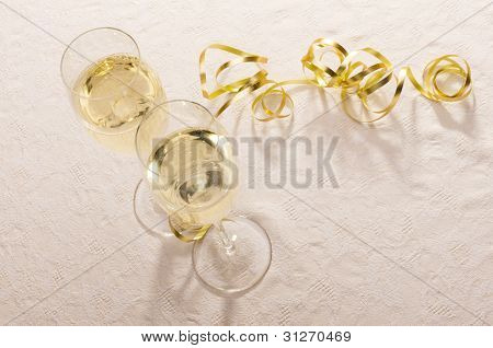 Champagne Glasses With Gold Ribbon On Pale Pink Tablecloth