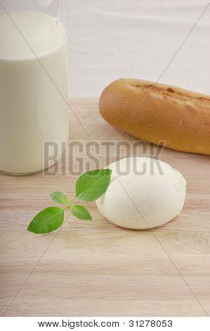 fresh mozzarella on chopping board with tomato milk and basil