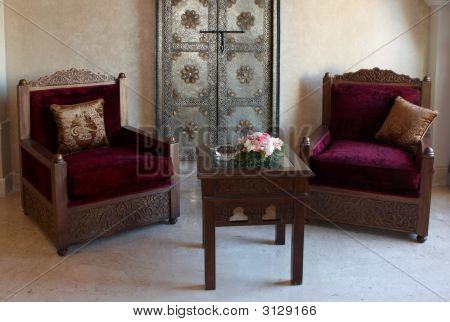 Old-fashioned Armchair And Table With Flowers