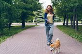 Cute Girl Student Is Walking With Shiba Inu Dog In Green Park Holding Smart Phone Smiling Enjoying S poster