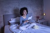 Beautiful Young Mixed Race Woman Wearing Pajamas Sitting On Bed, Eating Popcorn And Changing Channel poster