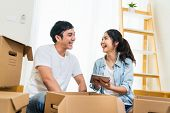 Happy Young Asian Couple Moving In To New House, Using Digital Tablet Organizing Things And Unpackin poster