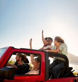 Five young adult friends on a road trip driving in an open top jeep by the sea poster