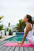 Side view of fit mixed-race woman performing yoga near swimming pool in the backyard. Summer fun at  poster